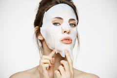 有看在白色背景的面部面具的女孩照相机 装饰性的程序 秀丽温泉和整容术 免版税库存图片
