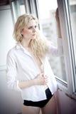 有看在窗口的白色衬衣的可爱的性感的金发碧眼的女人在白天 肉欲的长的公平的头发妇女佩带的女衬衫画象  免版税库存图片