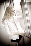 有看在窗口的白色衬衣的可爱的性感的金发碧眼的女人在白天 肉欲的长的公平的头发妇女佩带的女衬衫画象  免版税库存照片