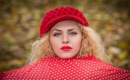 有看在红色伞室外射击的红色盖帽的可爱的白肤金发的女孩。秋天射击的可爱的少妇。 免版税库存图片