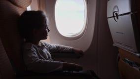 有看在飞机的棒棒糖的逗人喜爱的女孩窗口 股票录像