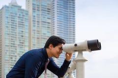 有看城市的双筒望远镜的亚裔商人 免版税库存图片