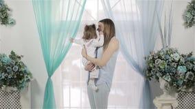 有看她的小的女婴的母亲站立在窗口附近和外面 影视素材