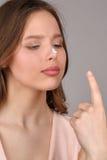 有看她的手指的奶油的女孩 关闭 灰色背景 免版税库存图片