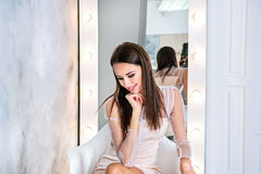 有看平直和柔滑的头发的年轻深色的妇女在镜子前面坐灰色背景和下来 库存照片