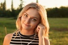 有看平直地在照相机的不可思议的微笑的一个好女孩 免版税库存图片