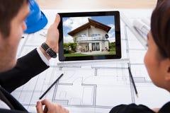 有看房子的数字式片剂的建筑师 库存照片