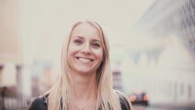 有看照相机和微笑的金发的少妇 美丽的女孩画象在城市迷离背景中 影视素材