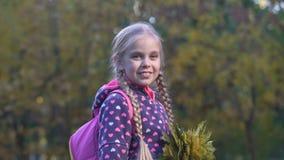 有看照相机和显示赞许的秋叶的美丽的女小学生 股票视频