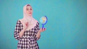 有看照相机微笑的地球模型的年轻美丽的回教妇女 股票视频