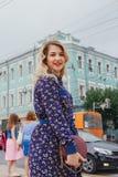 有看照相机的完善的brunnete头发的华美的年轻式样妇女摆在继续下去黑夹克的城市  库存照片