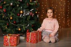 有看照相机的礼物盒的愉快的女孩 免版税库存图片