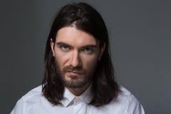 有看照相机的胡子和长的头发的严肃的人 免版税库存图片