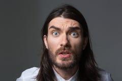有看照相机的胡子和长的头发的恼怒的人 免版税库存照片