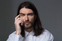 有看照相机的胡子和长的头发的沉思人 免版税图库摄影