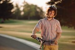有看照相机的自行车的白种人人 库存照片