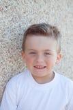 有看照相机的蓝眼睛的微笑的男孩 免版税库存图片