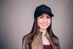 有看照相机的迷人的微笑的美丽的年轻深色的妇女 佩带一黑棒球帽和棕色皮革ja的女孩 图库摄影