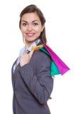 有看照相机的购物袋的时髦的女人 免版税库存照片