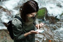 有看电话,瀑布背景的背包的年轻美丽的女孩 免版税库存图片
