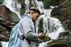 有看电话,瀑布背景的背包的年轻英俊的人 库存照片