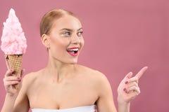 有看的甜点的愉快的白肤金发的女孩支持 免版税库存图片