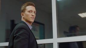 有看的英俊的商人对照相机有晚上后边玻璃窗背景 股票录像