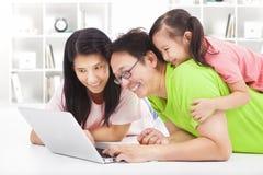 有看膝上型计算机的孩子的愉快的家庭 免版税库存图片