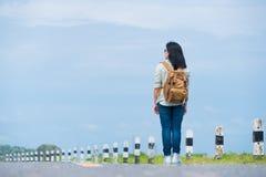 有看蓝天,亚洲妇女背包徒步旅行者的背包的旅客 图库摄影