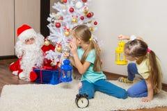 有看见设法谨慎地投入礼物在圣诞树下的圣诞老人的手电的女孩 免版税库存照片