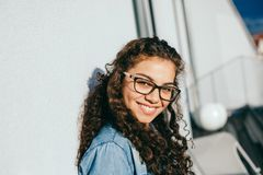 有看起来的卷发的年轻聪明的妇女微笑和看在照相机 免版税库存图片