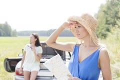 有看起来的地图的少妇去,当倾斜在敞篷车的朋友在背景中时 免版税图库摄影