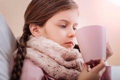 有看起来的杯子的小女孩生气 库存照片