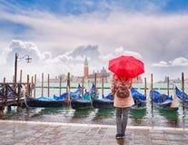 有看运河的全景一把红色伞的妇女重创,威尼斯,意大利 库存图片