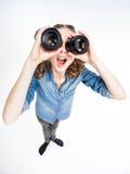 有看通过照片透镜的两马尾的逗人喜爱的滑稽的女孩广角 免版税图库摄影