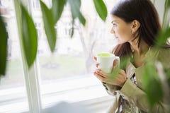 有看通过窗口的咖啡杯的年轻女实业家办公室 免版税库存图片