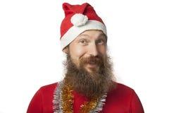 有真正的做疯狂的面孔和微笑,看和照相机的胡子的愉快的滑稽的圣诞老人和红色帽子和衬衣 图库摄影
