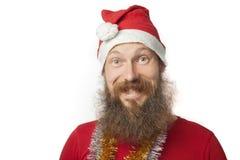有真正的做疯狂的面孔和微笑,看和照相机的胡子的愉快的滑稽的圣诞老人和红色帽子和衬衣 库存照片