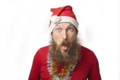 有真正的做疯狂的面孔和微笑,看和照相机的胡子的愉快的滑稽的圣诞老人和红色帽子和衬衣 免版税库存照片