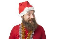 有真正的做疯狂的面孔和微笑,看和照相机的胡子的愉快的滑稽的圣诞老人和红色帽子和衬衣 免版税图库摄影