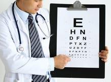 有眼力检查桌的医学医生举行大剪贴板垫 免版税库存照片