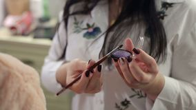 有眼影膏的一个调色板和构成刷子在化妆师` s手上 影视素材