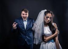 有眼泪汪汪的面孔的新娘和可怕的残酷新郎 免版税图库摄影