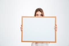 有眼睛大开偷看的少妇从空白的委员会 库存图片