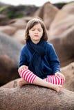 有眼睛的健康瑜伽孩子结束了坐在花岗岩石头 免版税库存图片