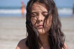 有眼睛的女孩闭上在海滩 免版税库存照片