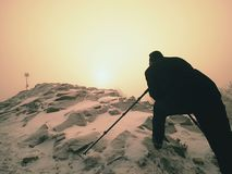 有眼睛的摄影师在照相机反光镜在三脚架逗留的在多雪的峭壁和拍照片 免版税库存图片