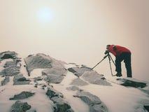 有眼睛的摄影师在照相机反光镜在三脚架逗留的在多雪的峭壁和拍照片 免版税图库摄影