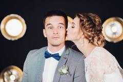 有眼睛的滑稽的新郎打开由他有辫子发型的美丽的新娘宽亲吻 免版税库存照片