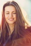 有眼睛的美丽的女孩结束了享用太阳 免版税库存图片